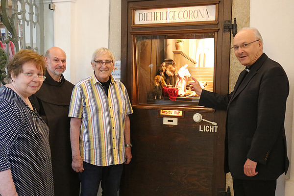Jahreskrippe mit Darstellung der 'Hl. Corona' mit Bischof R. Voderholzer, den Krippenbauer Ehepaar Pöllmann und F. Tarsizius Herrgesell OCD
